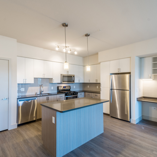 The Braydon - Fully Equipped Kitchen With White Upper And Lower Wood Grain Cabinets With Stainless Steel Appliances And Breakfast Island